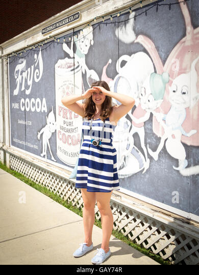 A happy young lady shields her eyes from the sun in front of a Fry's Cocoa billboard at Fort Edmonton Park in - Stock Image