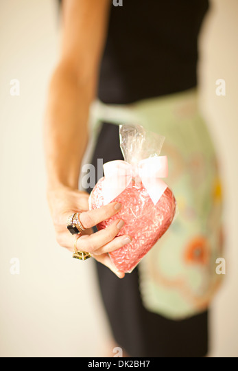 Close up midsection of woman in apron holding wrapped heart-shape Valentine's Day cookie - Stock Image
