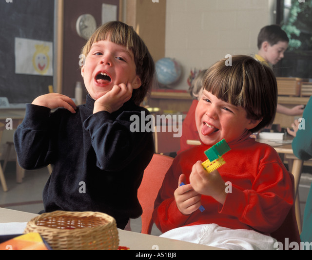 Male twins laughing on preschool class - Stock Image