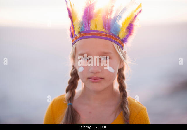 Portrait of girl dressed as native american with feather headdress - Stock Image