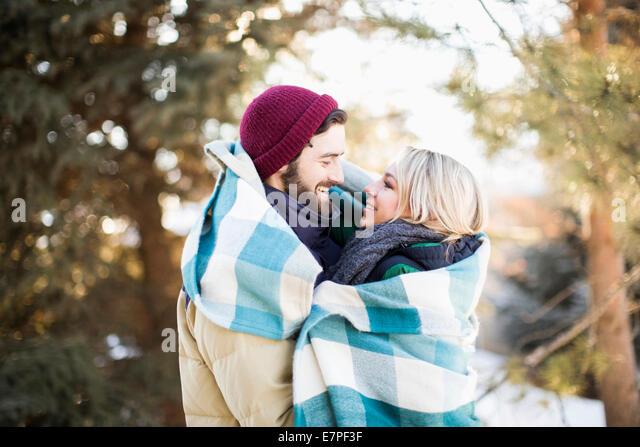 USA, Utah, Salt Lake City, Couple wrapped in blanket hugging outdoors - Stock-Bilder