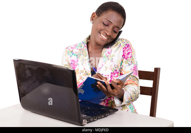 Young businesswoman sitting at the desk, her laptop in front of her communicating taking notes - Stock Image