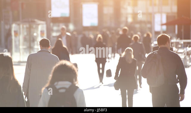 abstract crowd of people walking on the street, unrecognizable silhouettes with back light - Stock Image