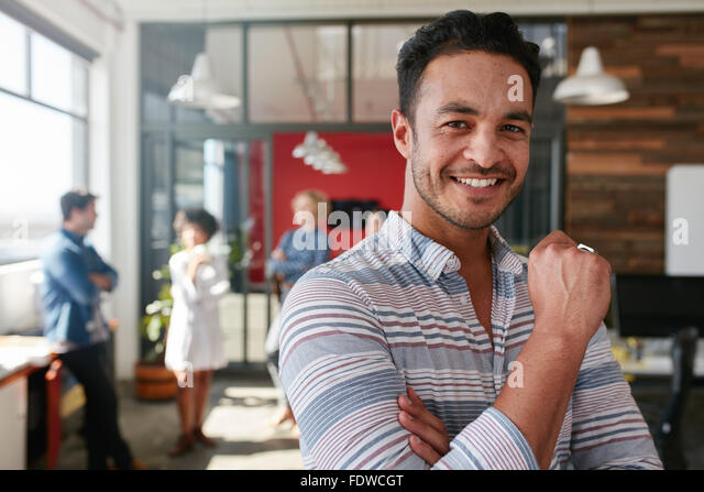 Portrait of smart creative professional looking at camera and smiling. Happy caucasian man standing in office with - Stock Image