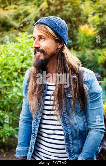 Mid adult man with long hair, wearing hat - Stock Image