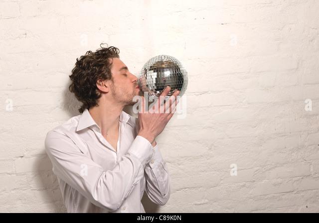 Germany, Hamburg, Mid adult man kissing mirror ball - Stock-Bilder