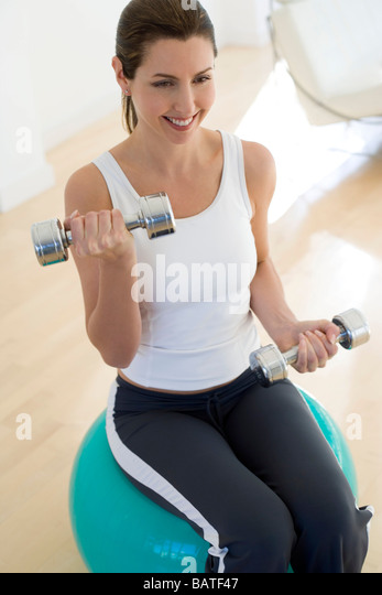 Weightlifting. Woman liftingdumbbells whilst sitting on an exercise ball. - Stock Image