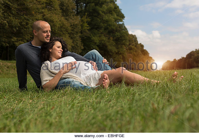 Pregnant couple sitting on grass in park - Stock Image
