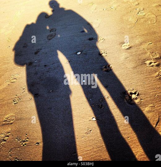 Shadow of a couple on the beach - Stock Image
