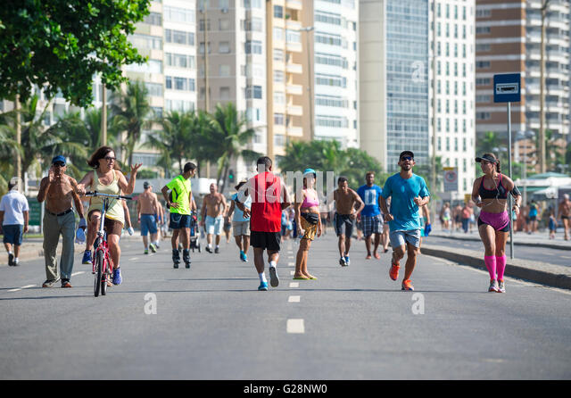 RIO DE JANEIRO - APRIL 3, 2016: Joggers and walkers share the beachfront Avenida Atlântica on a car-free morning - Stock Image