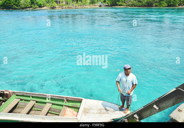 Man standing on his boat by the river in Labuan Cermin - Stock Image