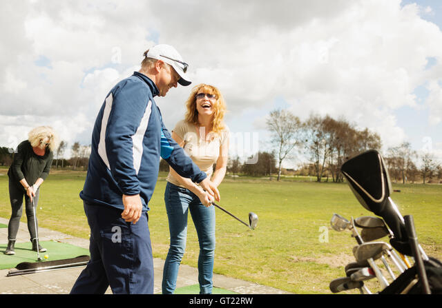 Happy friends practicing golf at driving range on sunny day - Stock-Bilder
