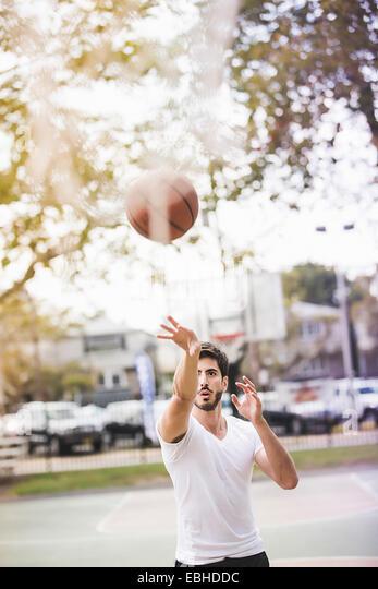 Young male basketball player throwing ball to basketball hoop - Stock Image
