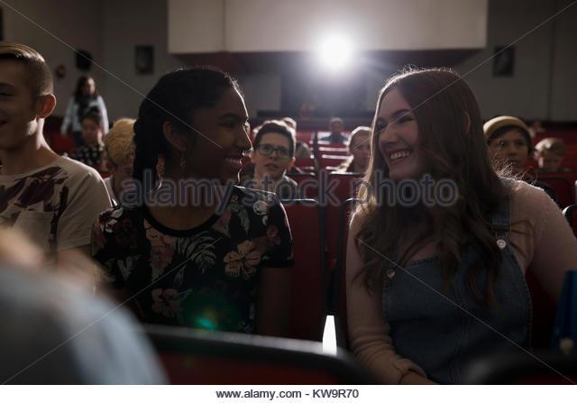 Smiling tween girl friends watching movie in dark movie theater - Stock Image
