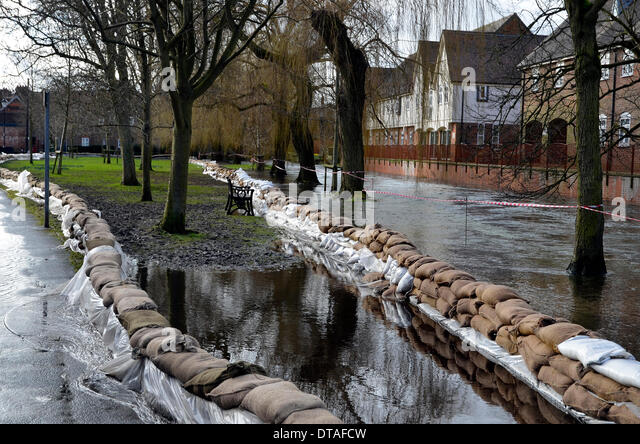 The River Itchen overflows along Water Lane close to the city centre of Winchester, the county town of Hampshire. - Stock Image