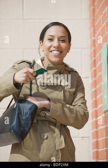 Hispanic woman standing in front of a bank access slot - Stock-Bilder