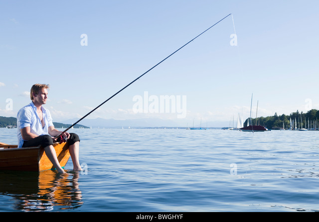 Businessman with fishing rod in rowboat - Stock Image