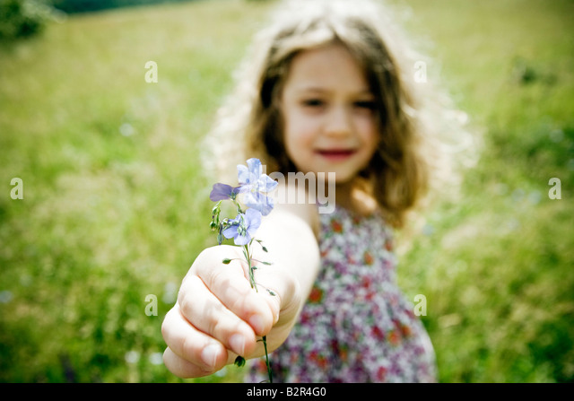 Girl holding flower to camera - Stock Image