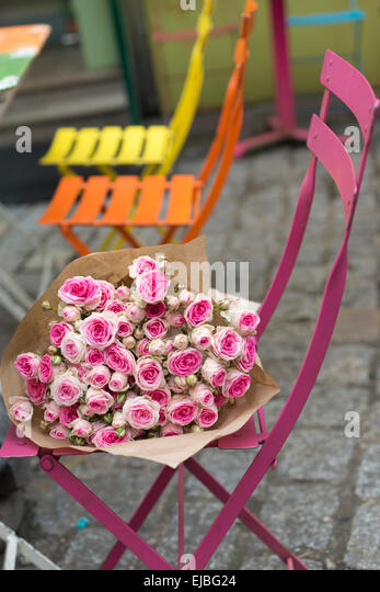 Pink cut Mimi Eden spray roses on cafe chair Paris, France - Stock Image