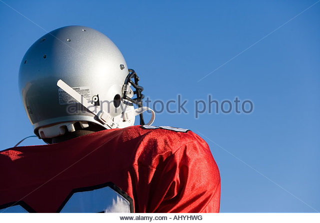 American football player wearing red football strip and protective helmet, standing against clear blue sky, close - Stock Image