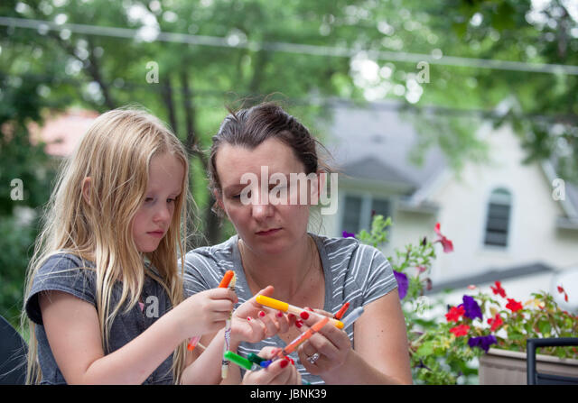 Mother and daughter working on the deck selecting colors for an art project. St Paul Minnesota MN USA - Stock Image