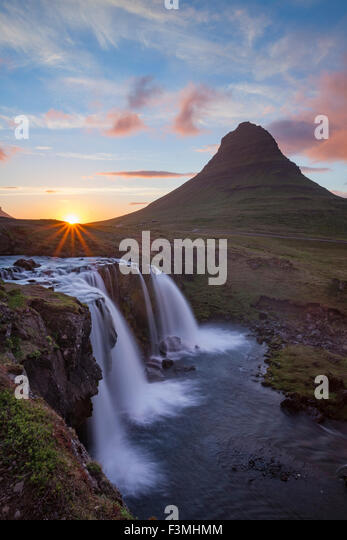 Sunset over Kirkjufell mountain and waterfall, Grundarfjordur, Snaefellsnes Peninsula, Vesturland, Iceland. - Stock-Bilder