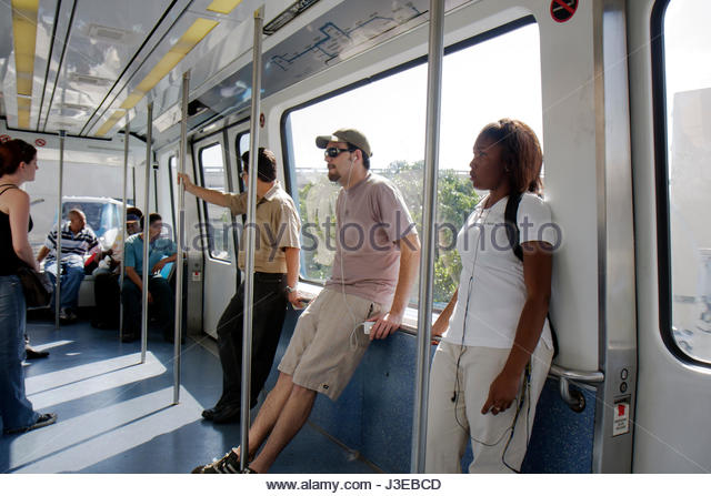 Miami Florida Metromover downtown free automated people-mover system passengers commuters Black woman men public - Stock Image