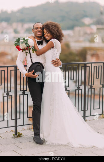 Happy black bride and groom softly hugging on the terrace with cityscape on background - Stock-Bilder