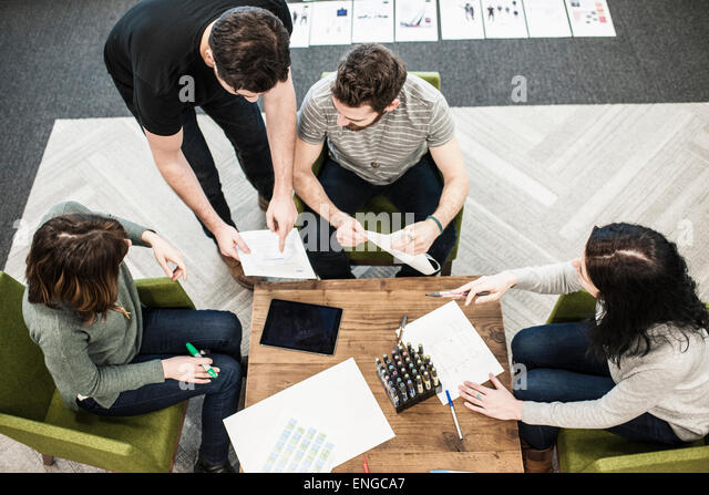 Four people seated at a table using coloured pens on paper, colleagues at a planning meeting. - Stock Image