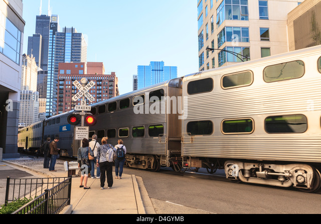 Metra Train passing pedestrians at an open railroad crossing, Downtown, Chicago, Illinois, USA - Stock Image