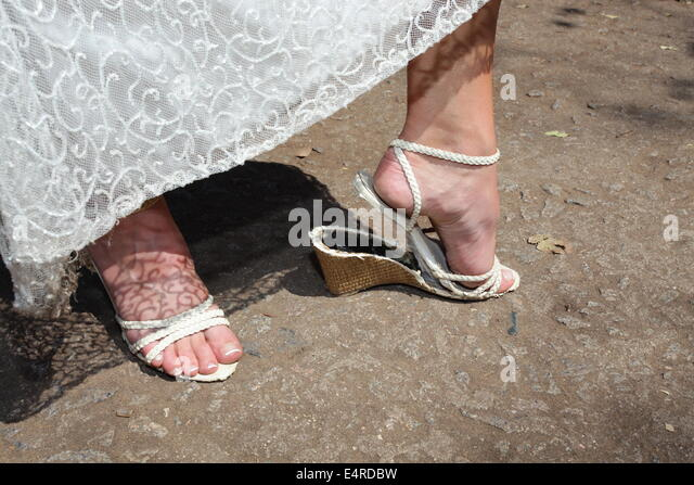 Funny take on a wedding as the brides shoe has broken - Stock Image