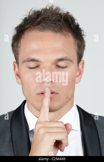 Portrait of businessman showing silence gesture with his forefinger by mouth - Stock Image