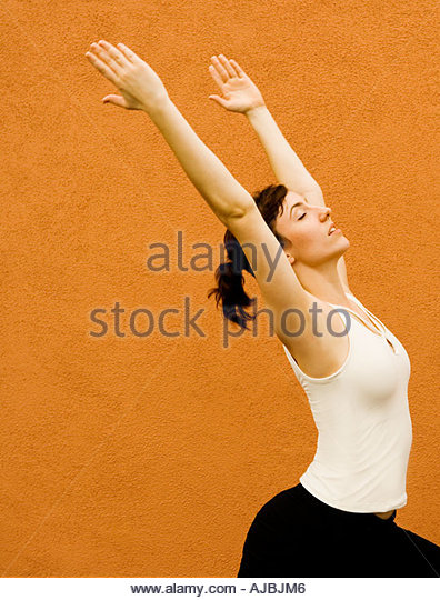 Adult woman in Yoga like stretch pose with strength beauty balance and grace  in front of  Terracotta Colored  Wall - Stock Image