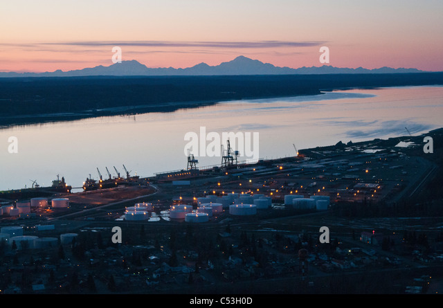 Aerial evening view of the Port of Anchorage with Mt. Foraker, Mt. Hunter and Mt. McKinley in the background, Alaska, - Stock Image