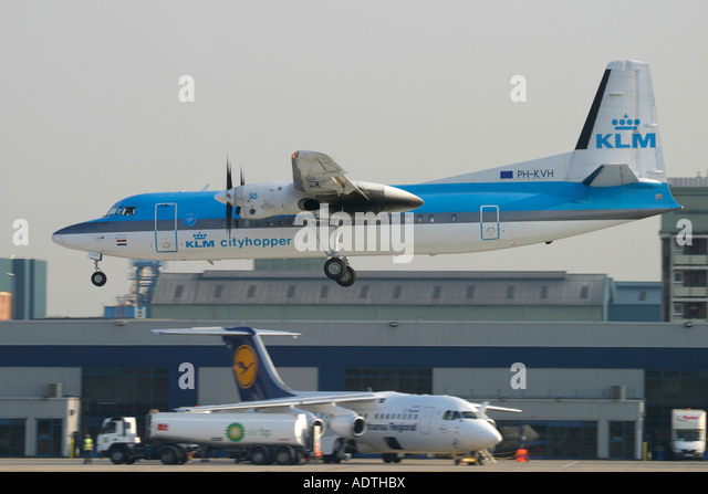 KLM Cityhopper regional aircraft landing and Lufthansa jet in the background at London City Airport England UK - Stock Image