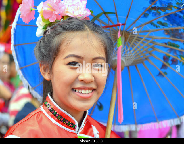 Smiling Thai Chinese Girl in Traditional Dress with Blue Parasol, Northern Thailand. - Stock Image