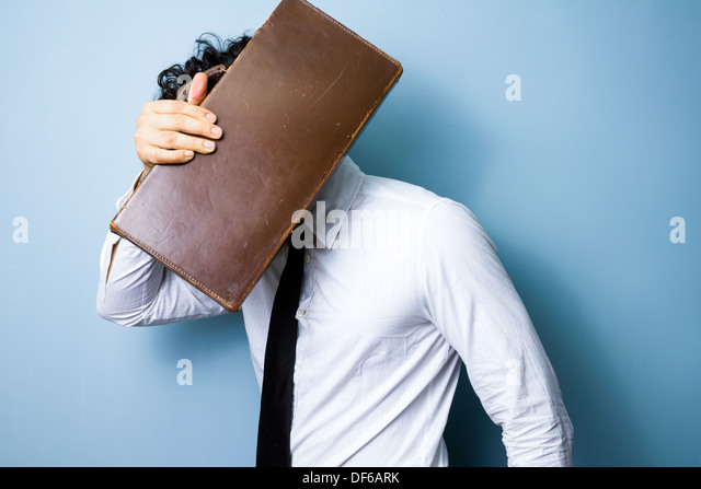 Young businessman is hiding his face behind a briefcase - Stock Image