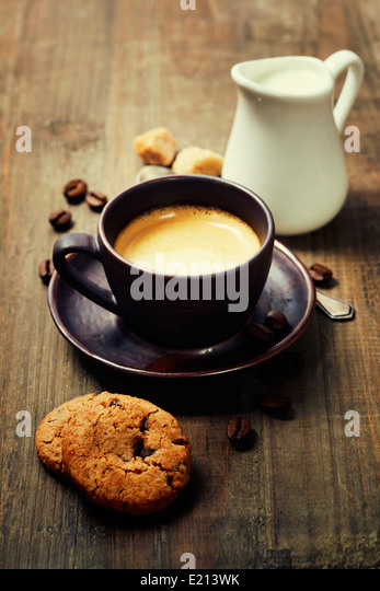 Coffee, milk and cookies on wooden background - Stock Image