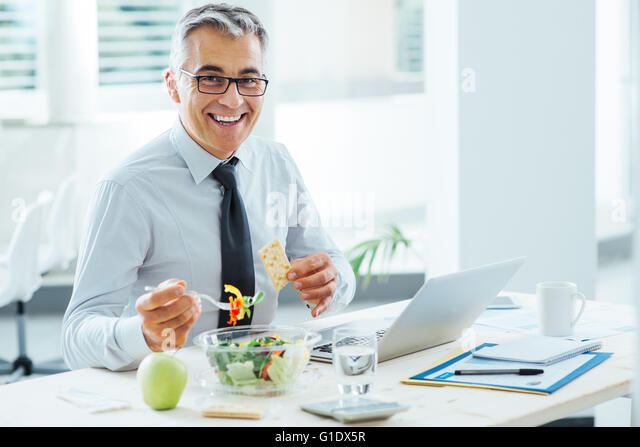 Smiling businessman sitting at office desk and having a lunch break, he is eating a salad bowl - Stock Image
