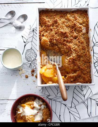 Dish of peach ginger crisp - Stock Image