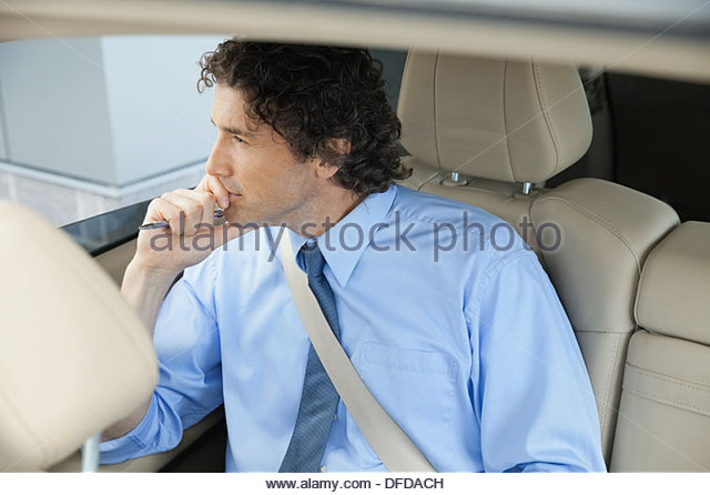 Thoughtful businessman looking out car window - Stock Image