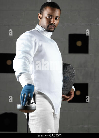 Fencer wearing fencing uniform in a gym - Stock Image