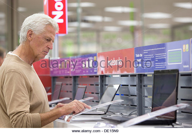 Senior man looking at prices on laptops in electronics store - Stock Image