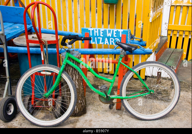 Belize City colorful old bicycle chained to post at Wet Lizard Bar Belize Tourism Village - Stock Image