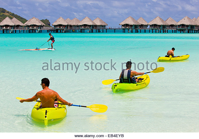 Tourists kayaking and wind surfing off the coast of Bora Bora. - Stock Image