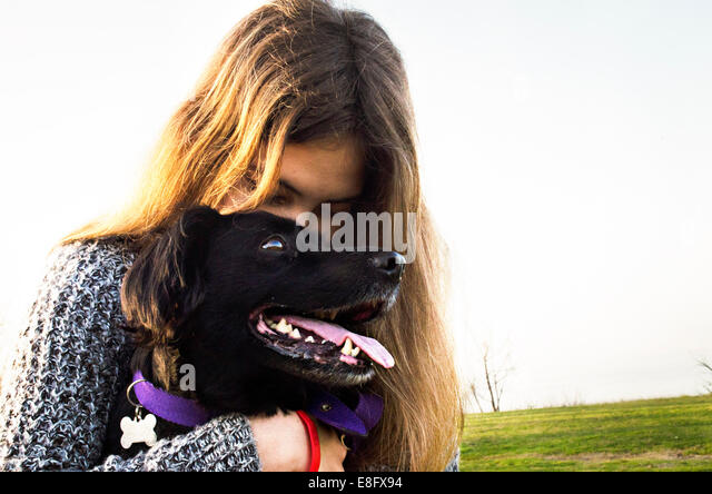 Argentina, Buenos Aires, View of teenage girl (14-15 years) hugging dog - Stock Image