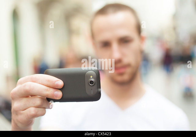 Urban photographer with mobile phone make photo on street - Stock Image