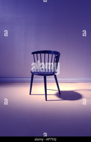modern chair stands alone in room dramatic light - Stock Image