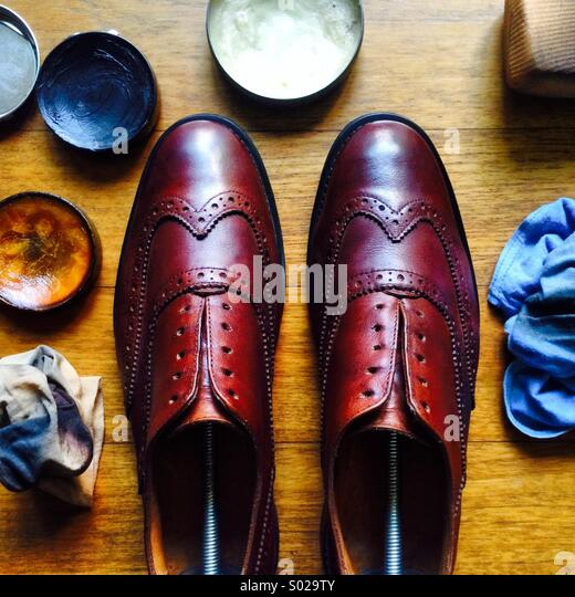 A pair of brown wingtip brogues lined up after a polish and cleaning work, surrounded by polishing tools - Stock-Bilder