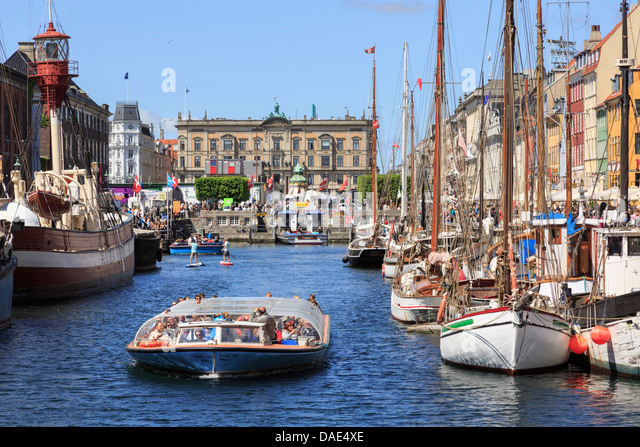 Tourists on canal tour boat with old wooden boats moored in Nyhavn harbour, Copenhagen, Zealand, Denmark, Scandinavia - Stock Image